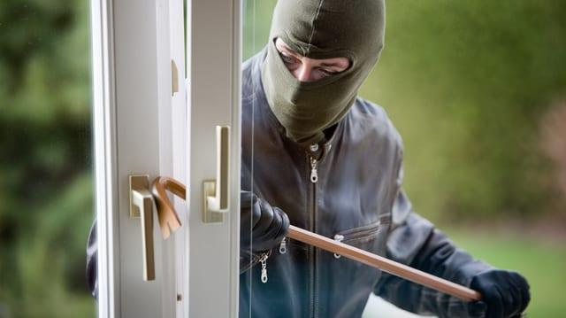Maskierter wuchtet Glastüre auf.
