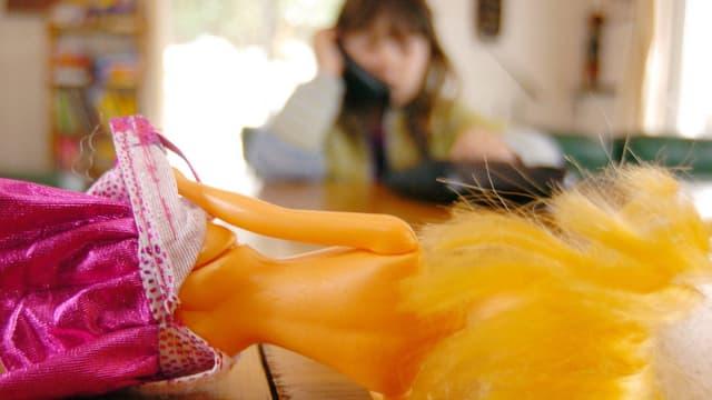 Eine halbnackte Barbie-Puppe, dahinder ein kleines Mädchen.