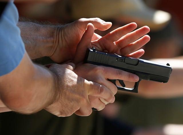 Hände an einer Waffe.