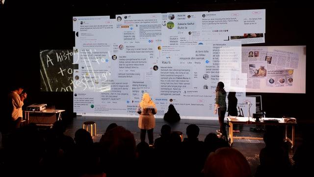 Menschen vor Bühne mit Leinwand und Projektionen