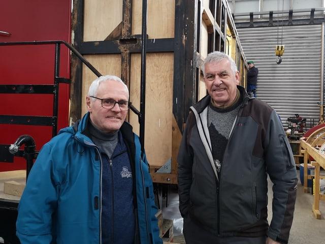 Zwei Männer vor Bahnwagen.