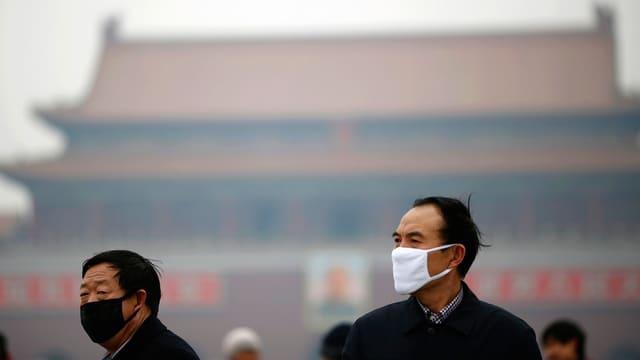 Zwei Männer mit Gesichtsschutz. Hinter ihnen vernebelt der Smog die freie Sicht auf ein Haus.