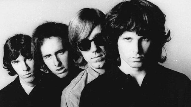 Schwarz-Weiss-Foto: Die vier Bandmitlieder stehen versetzt hintereinander und blicken in die Kamera.