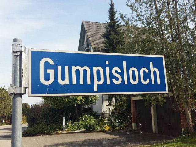 Auf einem Strassenschild steht Gumpisloch.