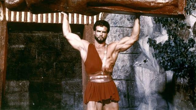 Ein sehr muskulöser Mann mit wenig an trägt eine Statue.