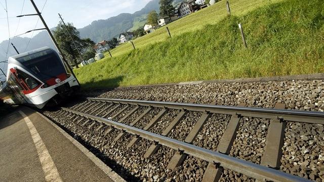 Ein Zug, der auf einem Gleis angefahren kommt.