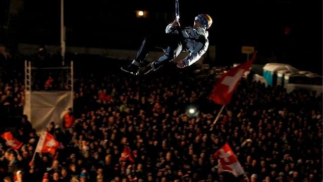 Carlo Janka hängt an einem Seil, unter ihm tausende Zuschauer.