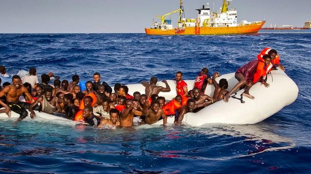 Afrikaner auf einem Gummiboot, das schon halb unter Wasser steht. Hinten ein Schiff.