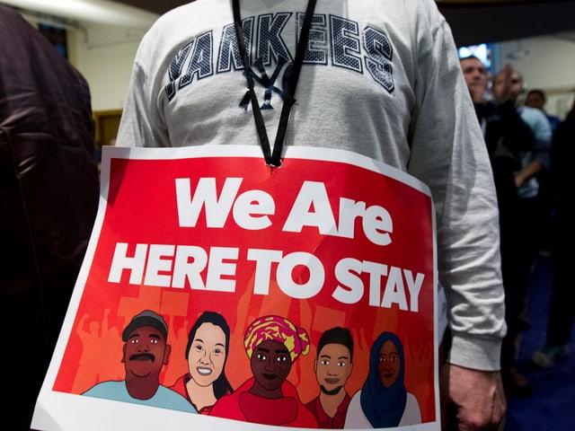 Demonstrant mit Schild «Wir sind da um zu bleiben»
