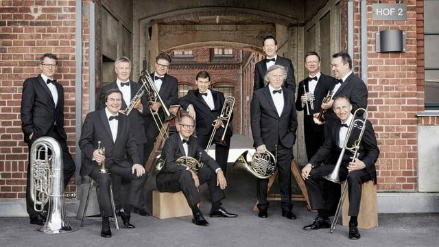11 Männer mit Anzug und Blasinstrument.