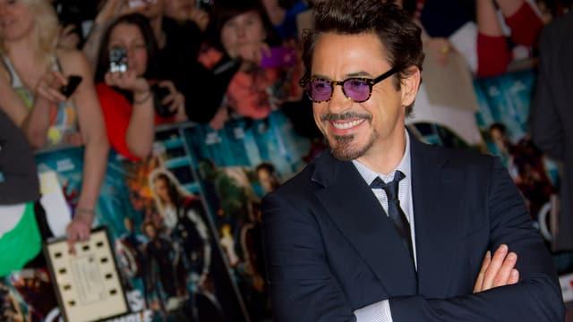 Robert Downey Jr. im schwarzen Anzug lächelt in Richtung Fans.