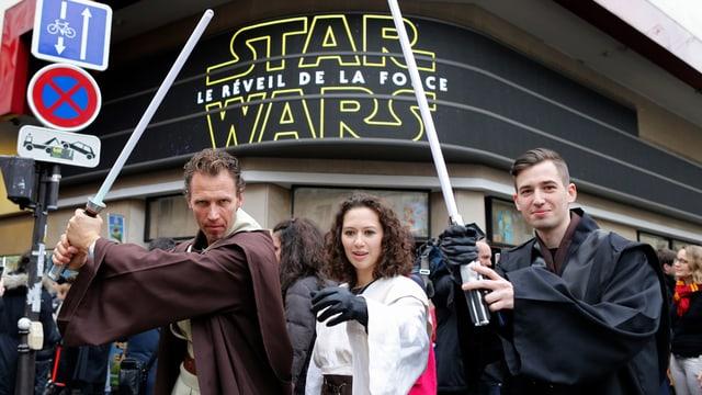 Drei Kinogänger in Star-Wars-Kostümen Laserschwertern vor einem Pariser Kino
