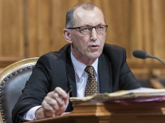 Mann spricht in ein Mikrofon im Ständeratssaal.