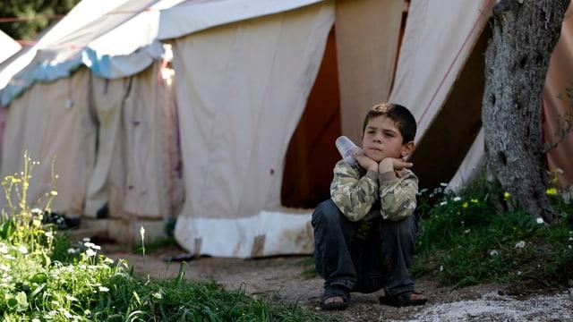 Ein syrischer Knabe sitzt vor Zelten eines Flüchtlingscamps in Libanon.