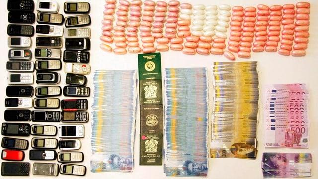Aufgereite Handys, Drogendäumlinge, Geld und Pässe.