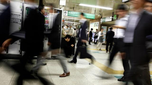 Japaner eilen durch einen Bahnhof.