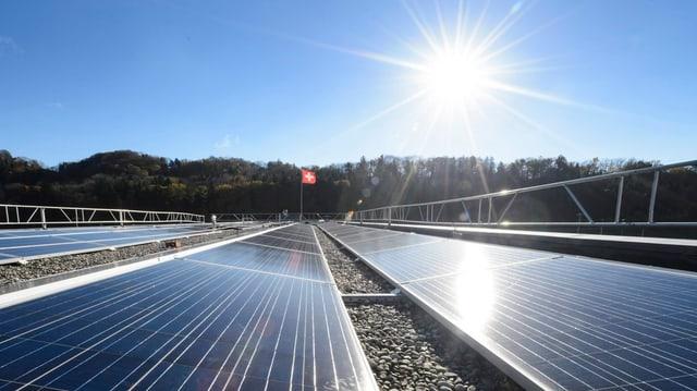 Sonne scheint auf eine Solaranlage in Daillens in der Romandie, Schweizerfahne weht im Hintergrund.