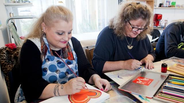 Zwei Frauen sitzen an einem Tisch und malen und zeichnen.