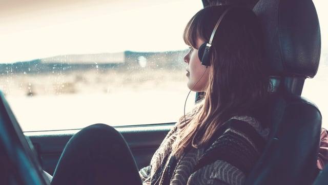 Eine junge Frau sitzt im Auto und hört über Kopfhörer Musik.