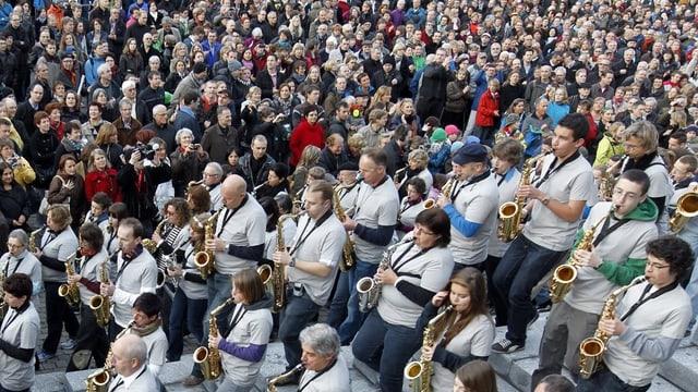 Eine Gruppe Saxophonspieler vor hunderten von Zuhörerinnen.