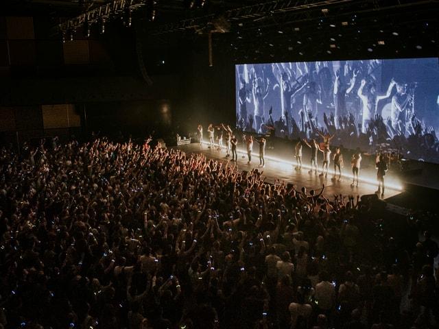 Konzerthalle, Publikum im Vordergrund, hinten die Bühne mit Band und LED-Screen