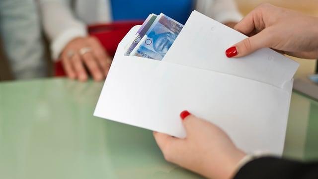 Eine Frau steckt 100-Franken-Noten in einen weissen Umschlag.