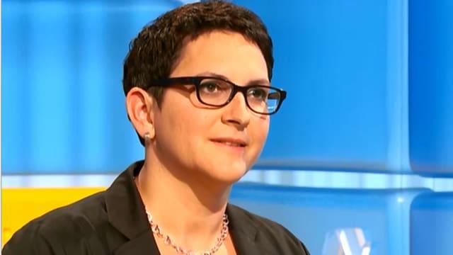 Kopf einer Frau mit kurzen Haaren und Brille auf blauem Hintergrund