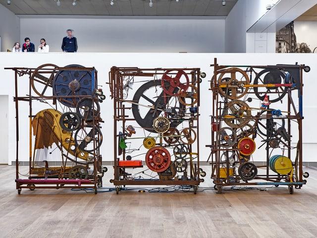 Ganze Maschine, im Museum Tinguely. Man sieht, wie Leute sie von einem Zwischenstock aus von oben ansehen.
