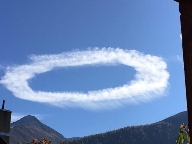 Weisser Kondensstreifen am blauen himme. An gewissen Stellen sind feine weisse Schleier unterhalb des Streifens zu sehen.