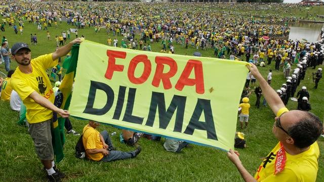 Demonstrants cun t-shirt mellen tegnan in placat cun l'inscripziun Fora Dilma