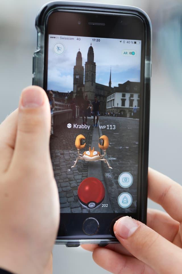 Jemand spielt Pokemon Go in Zürich.