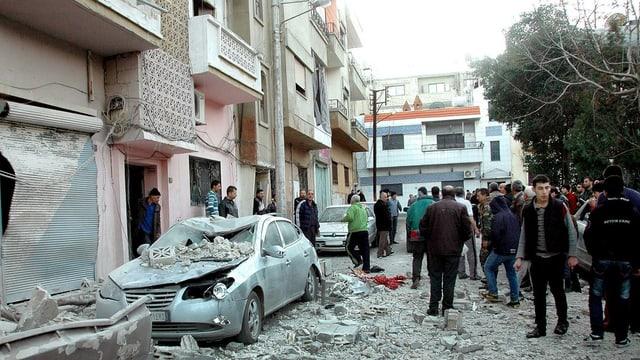 Einwohner von Homs besichtigen Schäden an Fassaden und Fahrzeugen
