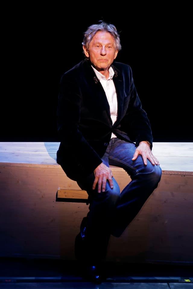 Roman Polanski sitzt auf einer Bank