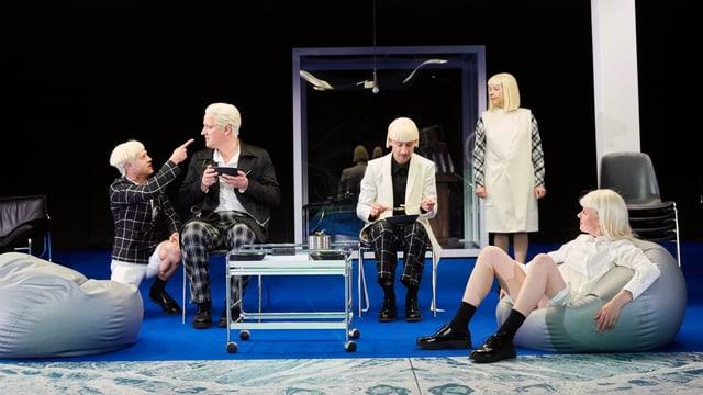 Schauspieler sitzen in Sitzsäcken und Bänken auf der Bühne.