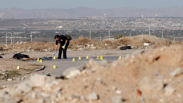Eine Polizistin beugt sich auf einer Brache über den Boden und sichert Spuren.