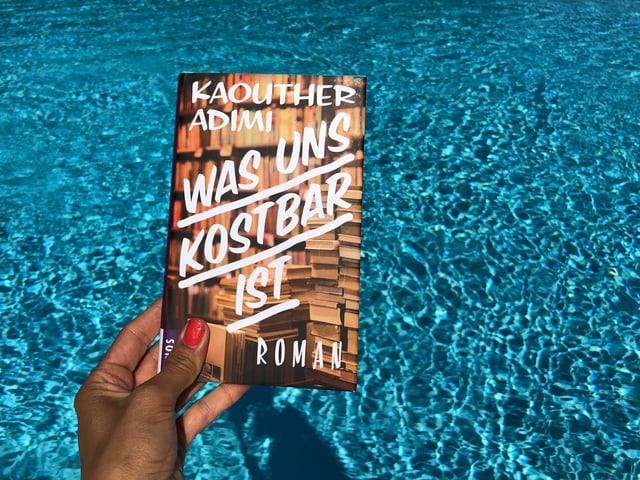 Annette König hält das Buch von Kaouther Adimi: «Was uns kostbar ist» vor blaues Wasser