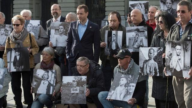 Ehemalige Verdingkinder und Opfer von fürsorgerischen Massnahmen posieren mit Kinderfotos vor dem Bundeshaus.
