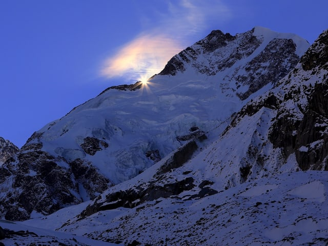 Die Sonne geht hinter dem Piz Bernina auf.
