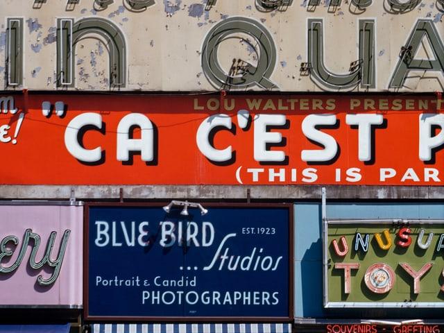 """Eine farbige Häuserfront mit der Aufschrift """"Ca C'est""""."""