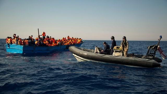 Britisches Schlauchboot nähert sich einem vollbesetzten Holzbötchen im Meer.