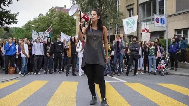 Eine Frau steht mit Megafon auf der Strasse.