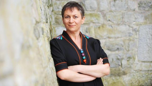 Anne Enright lehnt an einer wand. Sie hat kurzes Haar und trägt ein schwarzes Oberteil mit farbigen Kugeln.
