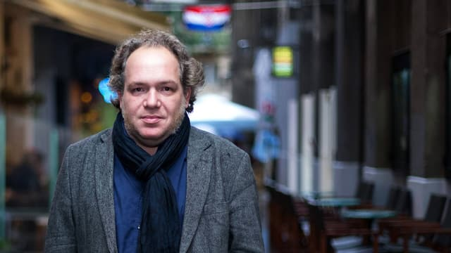 Ein Mann mittleren alters in grauem Jacket, blauem Hemd und schwarzem Haltuch steht in einer Strasse.