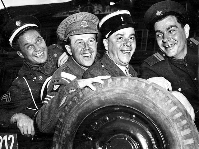 Vier uniformierte Männer stehen lachend hinter einem Pneu.