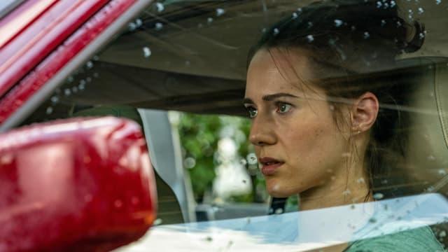 Rachel (Caren Pistorius) sitzt angespannt in ihrem Auto.
