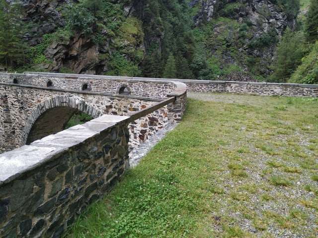 Eine alte Steinbogenbrücke über einen Fluss.