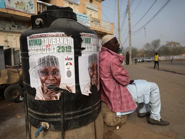 Mann lehnt an Säule mit Wahlplakat. Ärmliche Gegend.