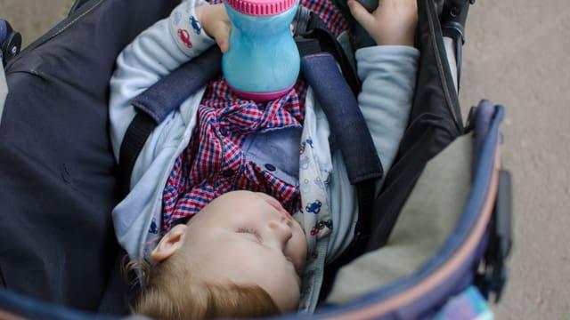 Ein kleines Kind schläft in einem Kinderwagen (Symbolbild).