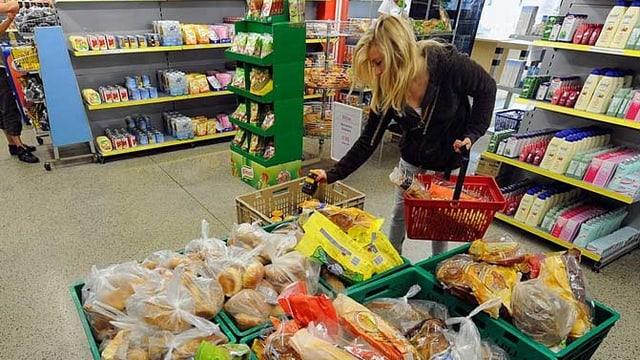 Eine Frau kauft in einem Caritas-Laden ein.