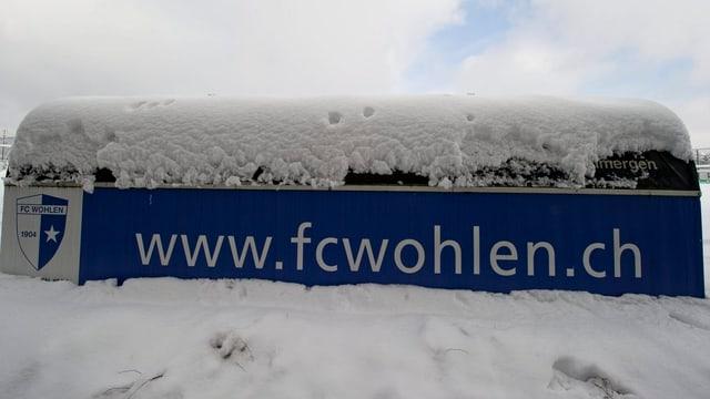 Schneebedecktes Plakat des FC Wohlen im Stadion Niedermatten.